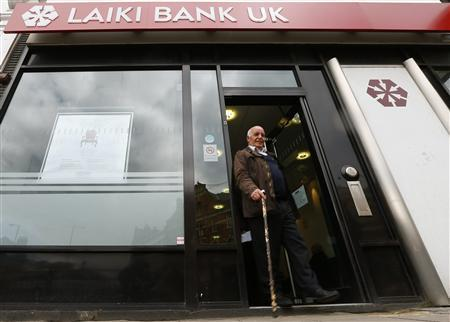 A customer walks out of a branch of Laiki Bank UK, in north London