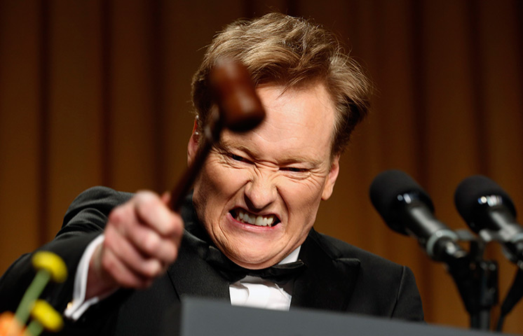 Comedian Conan O'Brien smashes a gavel as he speaks