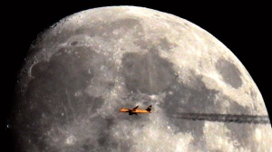 Plane against moon