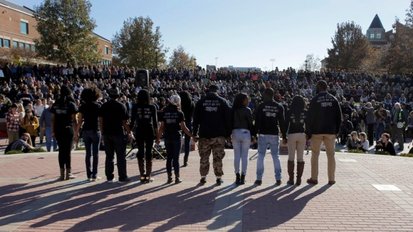 Members of black student protest group Concerned Student 1950 hold hands following the announcement that University of Missouri System President Tim Wolfe would resign Monday, Nov. 9, 2015, at the university in Columbia, Mo. Wolfe resigned Monday with the football team and others on campus in open revolt over his handling of racial tensions at the school. (AP Photo/Jeff Roberson)