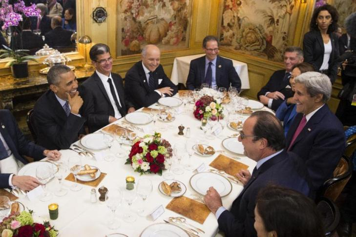 President Barack Obama, left, sits with French President Francois Hollande, bottom, as they have dinner at the Ambroisie restaurant in Paris, France, with Secretary of State John Kerry, right, and French Foreign Minister, Laurent Fabius, top 2nd right, Monday, Nov. 30, 2015. Obama is in France for a two-day visit as part of the COP21, the United Nations Climate Change conference. (AP Photo/Evan Vucci)